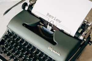 an image of a type writer with a piece of paper that says review