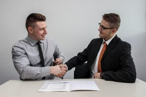 People shaking hands after signing a good contract